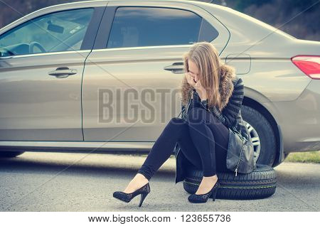 Woman sit on a wheel while a calling help. Woman is next to a car.