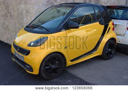 Saint-Paul-de-Vence France - March 22 2016: Yellow Smart Fortwo Cityflame Parked in the Street of Saint-Paul-de-Vence France