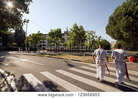 Spain Navarra Pamplona 10 July 2015 S Firmino fiesta two men dressed in the traditional clothes of the S Fermin festival go towards the city center to see bull running