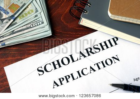 Scholarship Application on a table and dollars.