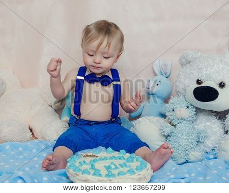 Happy baby boy eating cake by hands and feet for his first birthday party. Handsome little gentleman wearing the bow tie and suspenders.