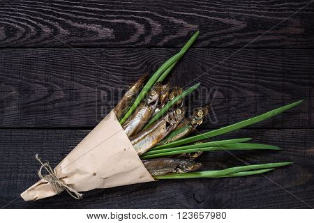 Smoked capelin with green onions in paper cornet on dark wooden background. Top view
