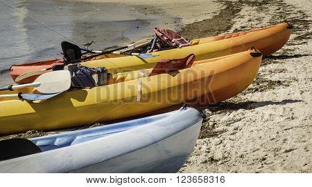 Kayaks - Three kayaks pulled up onto a sandy beach