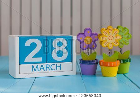 March 28th. Image of march 28 wooden color calendar on white background with flowers.  Spring day, empty space for text.
