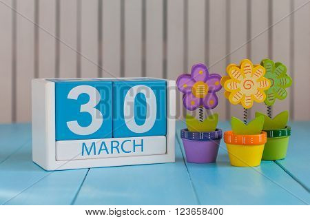 March 30th. Image of march 30 wooden color calendar on white background with flowers.  Spring day, empty space for text.