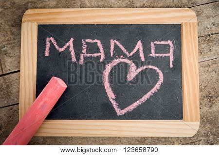 Old blackboard with Word Mama and a Heart, written with pink chalk, vintage wooden table