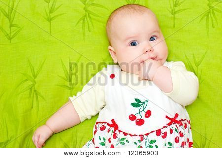 Cute little baby girl holding her hand in mouth