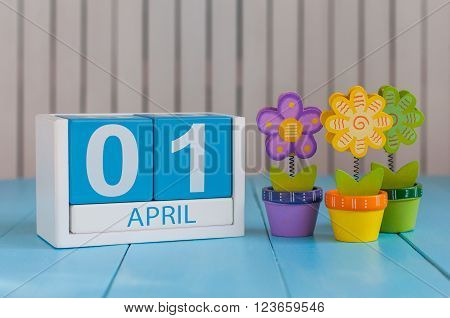 April 1st. Image of april 1 wooden color calendar on white background with flowers. Spring day, empty space for text. All Fool's Day.