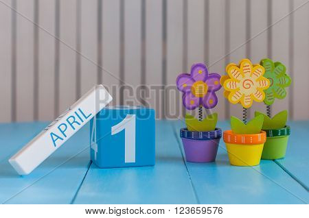 April 1st. Image of april 1 wooden color calendar on white background with flower. Spring day, empty space for text. All Fool's Day.