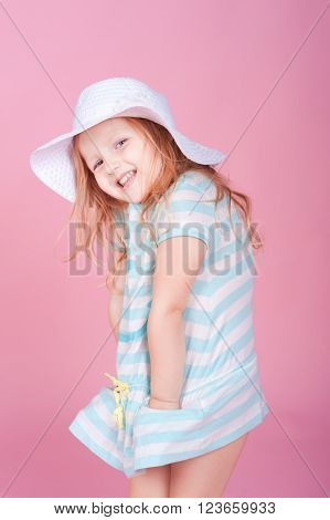 Smiling blonde kid girl 4-5 year old having fun in roo over pink. Cheerful looking at camera. Playful.