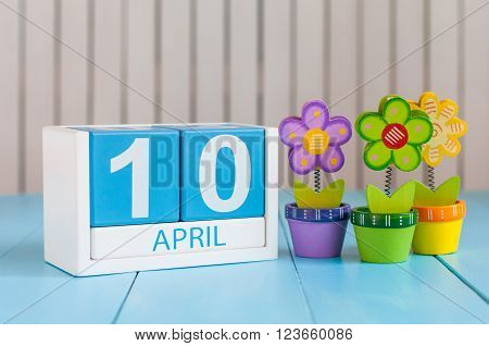 April 10th. Image of april 10 wooden color calendar on white background with flowers. Spring day, empty space for text. International Day Of resistance movement.