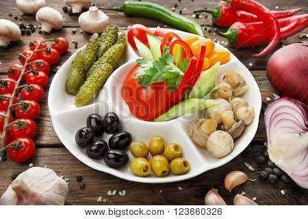 Restaurant appetizer food. Restaurant food assortment plate. Pickled vegetables, tomato, cucumber, peppers, olives platter in restaurant. Catering, served table. Pickled vegetables food plate.