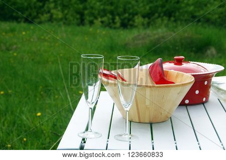 Picture of a picnic table with champagne glasses and tableware.