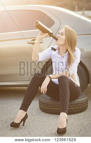 woman drink alcohol and sit on a wheel. Woman drink a alcohol. Sexy young woman. Repair a car. Car accident.