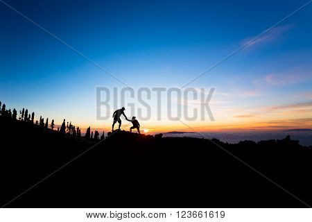 Teamwork couple helping hand trust help silhouette in mountains sunset. Team of climbers man and woman hikers help each other on top of mountain beautiful inspirational sunset landscape on Tenerife Canary Islands