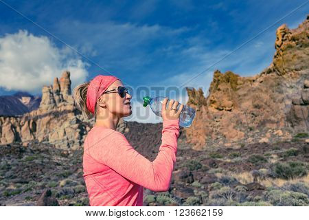 Trail runner woman drinking water and running in mountains, inspirational landscape. Training and working out jogging and exercising outdoors in nature, rocky footpath on Canary Islands, Spain.