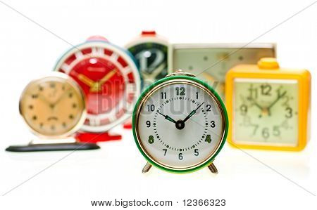 Vintage mechanical wind-up alarm clocks on white background, shallow focus