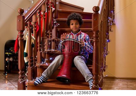 Afro child plays on drum. Kid with drum on Christmas. Young percussion talent. Call it his first concert.