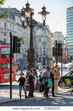 LONDON, UK - SEPTEMBER 10, 2015: People crossing the busy junction at Trafalgar square