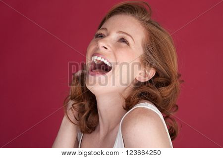 happy smiling woman with freckles on red with blue eyes