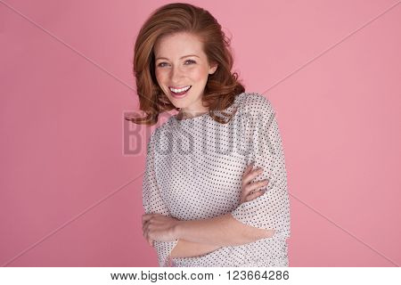 happy smiling woman with freckles on pink with blue eyes
