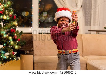 Afro boy holding Christmas petard. Little Santa with fire cracker. It will be loud. Happy holidays, dear neighbours.