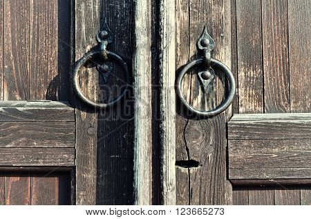 Wooden old weathered door with keyhole and worn metal door handles in the form of ring. Architectural detailed background in retro tones