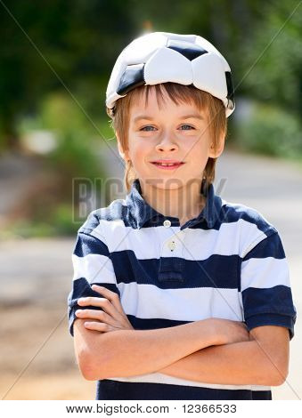 Young boy posing with a soccer ball on his head outdoors
