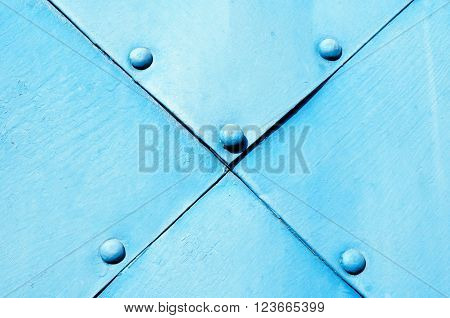 Metal light blue textured surface of old hammered metal plates with rivets on them. Grunge rough metal background.