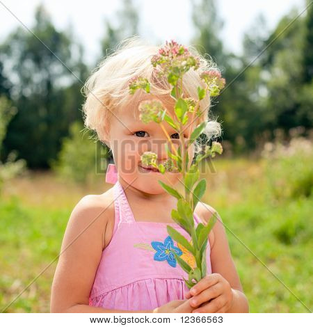 Portrait of cute little girl holding fower outdoors
