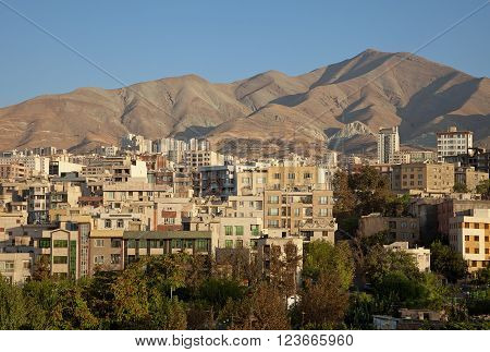 Skyline of Residential Buildings in Front of Brown Mountains and Clear Blue Sky of Tehran