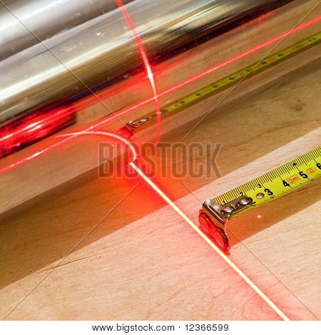 Measuring concept with tape measuring tool and red laser beam