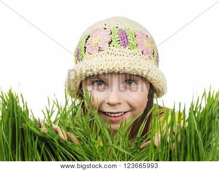 Beautiful little girl peeking out of the grass on a white background.