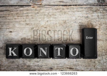 keys on a wooden table with the german word Konto, which means account, conceptual