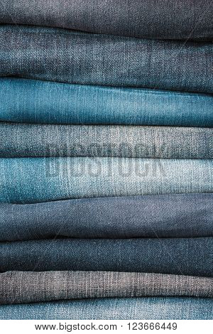 Stacked fashion jeans closeup, blue jeans background