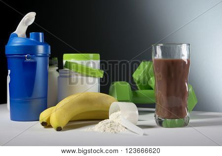 Sport Nutrition Supplement containers with glass of cocktail