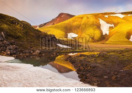 The golden light of dawn illuminates the mountains and glaciers national park Landmannalaugar, Iceland. Magic sunrise in the Arctic