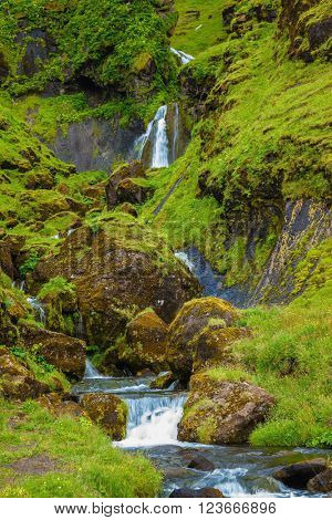 July in Iceland. Basalt mountains overgrown with a green grass and moss. Picturesque cascade step falls