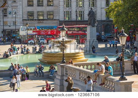 LONDON, UK - SEPTEMBER 10, 2015: Fountain and Lots of people and tourists on the Trafalgar square in hot summer day.