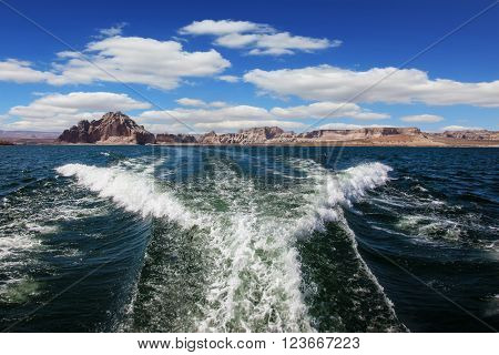 Lake Powell on the Colorado River. Stormy trace of motor boat crossing the emerald waters. In the distance the coast of red sandstone