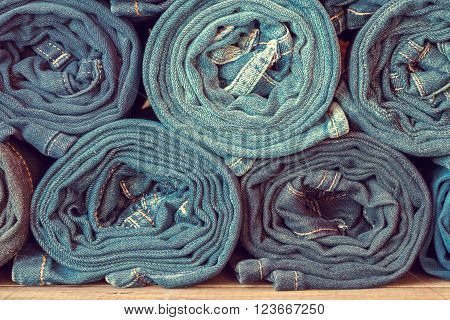 Rolled fashion jeans background, retro toned photo