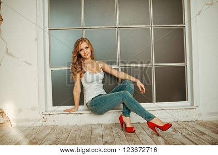 young woman sitting on the window sill, pretty girl sitting on a window sill, young woman sits near a window. ** Note: Visible grain at 100%, best at smaller sizes