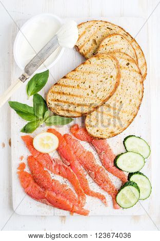 Ingredients for healthy sandwich. Grilled bread slices, smoked salmon, cottage cheese, cucumber nd basil on white wooden board, top view