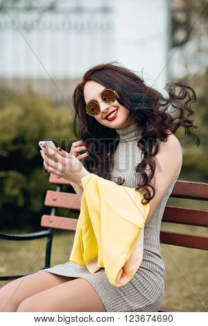 Bright stylish girl sitting on a bench and taking pictures of herself. Excellent Bright Makeup, red puffy lips, long dark hair, the girl has fun, goes crazy