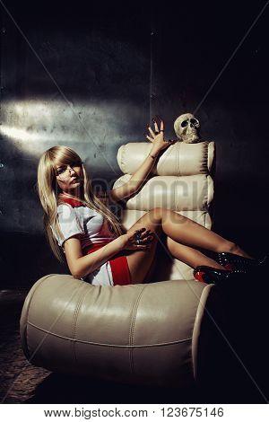 Seductive nurse with glasses sitting on an armchair