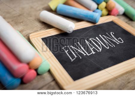 Slate with german word einladung, which means invitation, colorful crayon on wooden table
