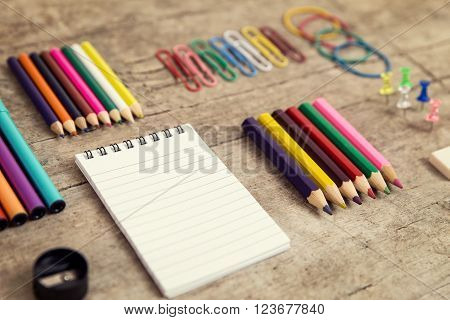 Office desktop with colorful pencils, notepad, supplies and paperclips, wooden table