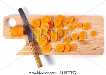 Fresh sliced carrot and knife on wooden chopping board