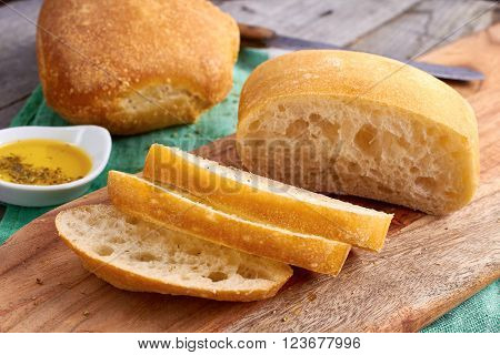 Sliced bread Ciabatta and virgin Olive oil on wooden background ** Note: Shallow depth of field