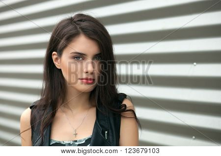 Closeup portrait of young beautiful brunette woman in black leather jacket posing outdoors against urban style background of metal strips